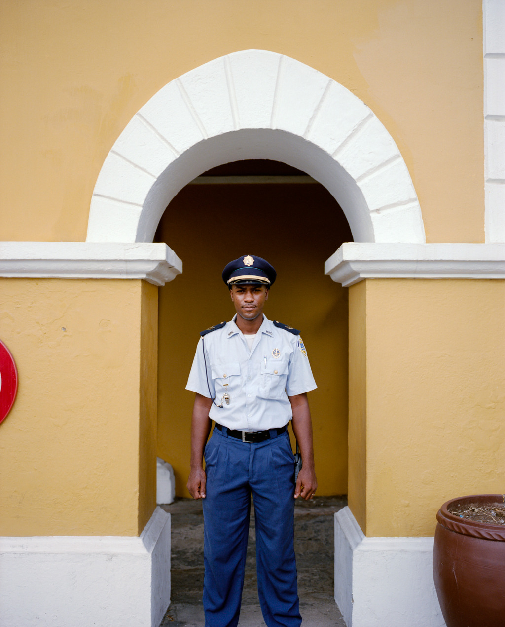 A young guard standing to attention (kinda) in front of the Governor's palace in Willemstad, Curaçao. Shot for enRoute magazine's February issue. Look for a full gallery of this assignment on my website in the coming days.