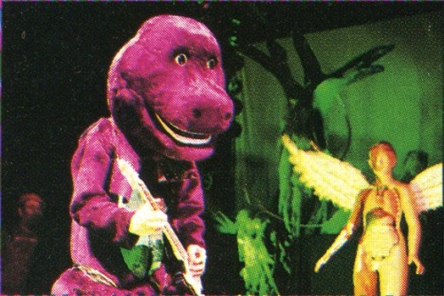 Kurt Cobain playing guitar in a Barney suit.