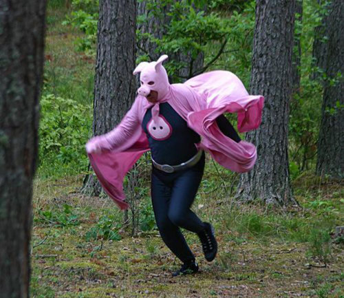 "Wearing a pink pig mask, cape, a silver belt and black spandex, this real-life superhero is known as Mr. Pigman. He patrols the forests of Latvia battling the forces of evil in the form of unscrupulous litterbugs:  ""Just look at this mess! Scoundrels! How could they litter like this?"" Mr. Pigman asks, pointing to mounds of trash sprawled across the side of the road. This snout-donning, snuffling super-swine spends his days charging around Latvia, trying to clean up the woods and make the littering culprits squeal for mercy. There is even a legend to accompany him. ""If you litter in the forest you will turn into a pig,"" Mr. Pigman's secretary, Ginta Bormane, warned. And this may be more than a bluff, as Mr. Pigman is not all ""oink."" ""Once a forest warden called us and said he'd found the remains of a car,"" Mr. Pigman recalled. ""By the serial number we managed to find the owner and fined him – 200 lats [US $400]"" When Mr. Pigman started his work six years ago, Latvia's forests had become a pig sty, rife with areas that looked more like garbage dumps. Since then, the Pig has saved their bacon. Mr. Pigman, who like all superheroes refuses to reveal his true identity, works with police, educates school children, lobbies parliament and keeps on the hoof, rooting out those who litter and raising public awareness. In fact, he has become quite a Latvian celebrity. ""The world has four superheroes: Superman, Batman, Spiderman and the Latvian Tsukmans – Pigman,"" he says. ""Pigman will work until the last plastic bag or last bottle is gone from the forest,"" said his secretary.  Photo via EatLiver, photographer unknown. [via Russia Today]"