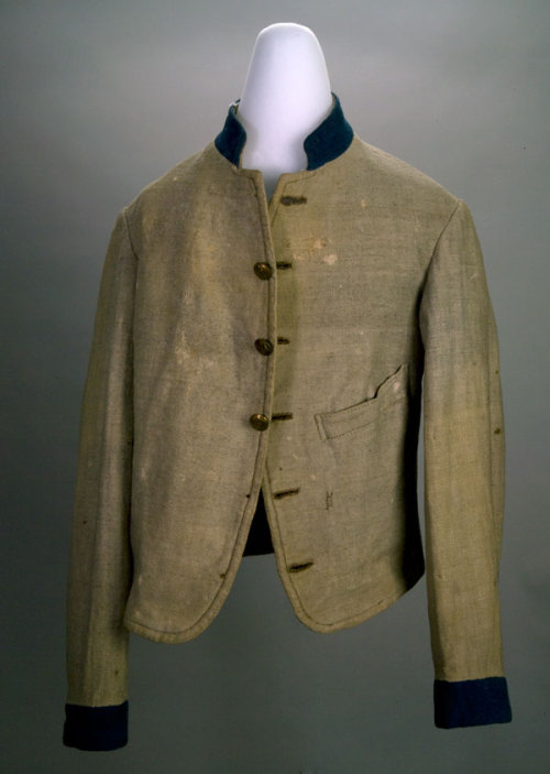 Confederate Uniform Coat of Gray Wool with Blue Trim Referred to as a Columbus Depot Style Jacket. Originally had six buttons. One pocket on the left front side as-well-as an inside pocket on the right side. The coat belonged to Private Michael Jackson Jones, who served with Company H, 1st Missouri Infantry. Private Jones was wearing the coat when he received a disabling wound at Champion Hill on May 16, 1863.  Wool. Shoulders (measuring across back just below collar) 39.0, Left Sleeve 60.0, Right Sleeve 60.0, Backseam 56.9 cm Credit:Vicksburg National Military Park , VICK 572