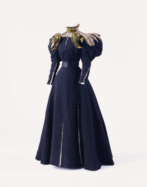 KCI: c. 1890 This is a Renaissance revival dress. The thick cloth of bouclé and smooth satin, the slits used effectively throughout the dress, and the decorations typical of the Renaissance revival all convey the nostalgia for the grand past which was felt at the end of the 19th century. After Gustave Beer opened a house in Vienna, they relocated their base of operations to Paris in 1905. Gustave Beer kept hold of their foreign clientele, and introduced their works during the season at a famous hotel in Paris.