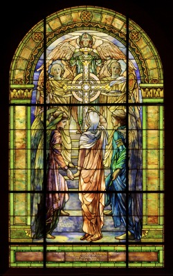 "This Tiffany Studios window demonstrates how the firm transformed the traditional art of stained-glass windows. Except for a few painted areas—the faces, hair, hands, and feet of the figures—the window's details are achieved through lead lines and colored, opalescent, and textured glass. Learn more about how Tiffany Studios created works like this in our newly refreshed ""Tiffany Studios"" gallery. The Righteous Shall Receive a Crown of Glory, United Methodist Church Window, Waterville, New York, about 1901–1902, Frederick Wilson (designer), Louis Comfort Tiffany, Tiffany Glass and Decorating Company or Tiffany Studios (studio), Stourbridge Glass Company or Tiffany Furnaces (glass), New York and Corona, NY. Gift of Mr. and Mrs. Bruce Randall. 96.4.230."