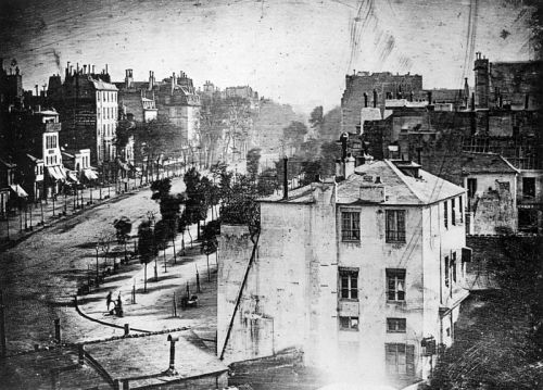 snapshotofhistory:  Boulevard du Temple, Paris - Daguerreotype by Daguerre. 1838. Believed to be the earliest photograph showing a living person. It is a view of a busy street, but because the exposure time was at least ten minutes the moving traffic left no trace. Only the two men near the bottom left corner, one apparently having his boots polished by the other, stayed in one place long enough to be visible.  Click pic for a huge version with fascinating detail.  goddamn look at that sexy-ass fascinating detail