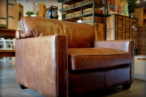 'Austin' armchair with distressed leather and stud design motif, from http://www.journeyeast.com