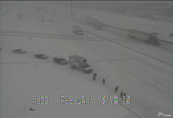 Motorists shovelling snow off the 401 near Toronto.