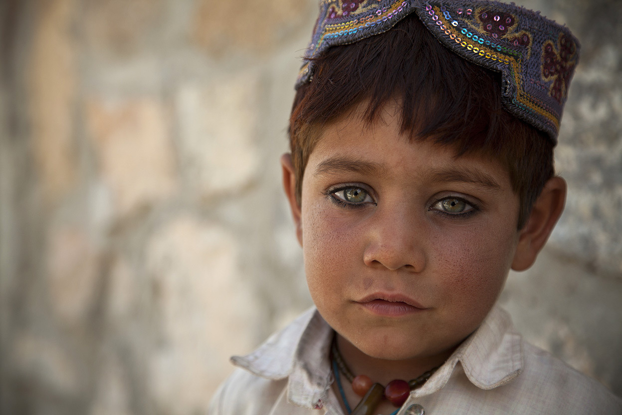 From Afghanistan: March 2013, one of 41 photos. Here, a child watches Afghan National Security Forces and coalition forces escort a district governor in Helmand province, Afghanistan, on March 17, 2013. (USMC/Sgt. Pete Thibodeau)
