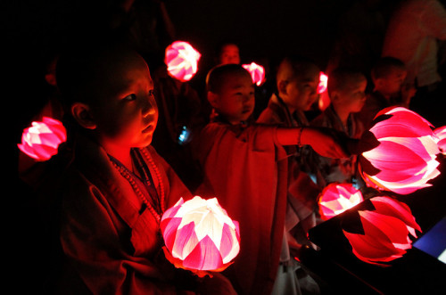 "fotojournalismus:  Boys taking part in ""Little Buddha Camp,"" in which they experience a monk's life for three weeks, hold lanterns while watching a video in Seoul, South Korea on May 15, 2013. [Credit : Ahn Young-joon/AP]"