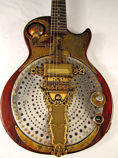 IonoGlobe electric guitar by Tony Cochran Guitars     The most unique feature of this electric guitar is the fully wired metal ball right by the neck. Farber Endison played this guitar in the late 50's for a band called The Bubble Tops. Their specialty was car oriented Rock-a-billy music before anyone wanted to hear it. When Farber's Uncle, Gropper T. Endison, was on safari in what is now known as Namibia, he had nearly been hit by a baseball size metal ball that fell from he sky. (This stuff still happens there. Google it.) He gave it to Farber claiming he could no longer bear the noises it made in his head. Farber's brother, Clayton, a hypothetical electrical genius, wired it to the guitar and told Farber that it would enhance the almost inaudible, and probably imagined, sounds emanating from the orb. It was probably not true. What we do know is that soon after, Farber grew out his hair, quit wearing shoes, and would only play the guitar in a cave found in the mountains behind his parents' house. He was found dead in 1965, deep in the cave with the guitar in his lap. There was a partially eaten sandwich and the diagram for five never before heard chords. To this day Clayton will not release them to the public.