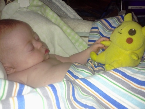 My little Pokemon master, holding hands with his Pikachu in his sleep.