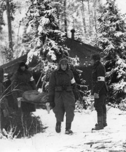 Finnish medics carrying the wounded on stretchers from a field hospital tent.