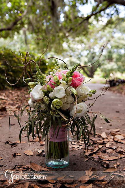 Ranunculus, peony, and snapdragons, with elongated eucalyptus and curly willow tendrils, wrapped in sheer ribbon. Image by Caroline Johnson Photography