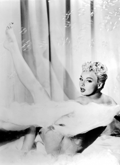 Burlesque dancer Lili St. Cyr on stage in her see-through bathtub c. 1950's