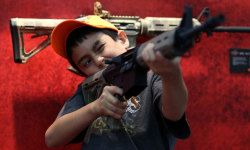 "guardiancomment:  'With the headlines about a five-year-old using a gun marketed as ""My First Rifle"" barely faded, the NRA invited attendees to ""[s]hare the excitement with spectacular displays and fun-filled events for the entire family"". The grade schoolers present shared the organization's attitude towards the products that have caused the deaths of more American children in two years than the very tragic US military casualties in Iraq and Afghanistan. ""I like guns because guns are fun,"" said 9-year-old Kaykay Mace' - Top 10 things you missed at the National Rifle Association Convention"