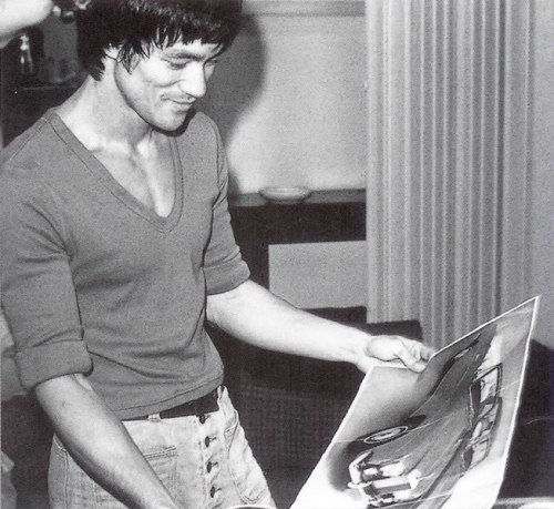 "Bruce Lee holding a picture of the gold Rolls Royce he ordered with the expected profits from ""Enter the Dragon."" Prior to ""Enter the Dragon"" filming, Bruce would often get giddy and constantly talk of the Rolls Royce to John Saxon and Jim Kelly.In order to receive the car, he was put on a six months waiting list but was over the moon knowing it would soon be delivered. Alas, Bruce actually died before ever setting eyes on the car and it was never delivered."