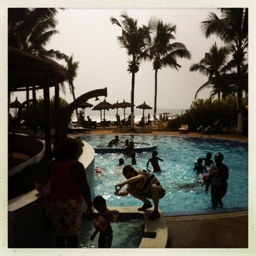 A man photographs a child by a hotel swimming pool in Grand-Bassam, Ivory Coast on January 13, 2013. Just outside if Abidjan, Ivory Coast's commercial capital, Grand-Bassam is a popular weekend destination for thousands of Ivorians. Photo by Peter DiCampo @pdicampo. #ivorycoast #grandbassam #abidjan #pool #beach #ocean #hotel #luxury #resort #travel
