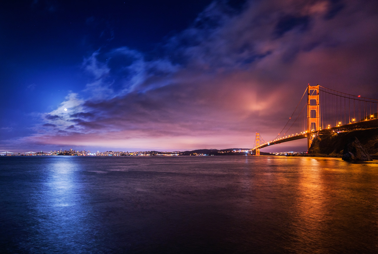 Duality  Ultra-wide San Francisco moonrise.  This one was taken the same day as these other two shots of mine, about an hour after the latter.  I wanted to capture both the moonrise and the heavy lighting of the Golden Gate Bridge, and the contrasting shades of blue and red those elements bestowed upon the scene. The 14mm made it easy, but not without distortion - I had to line the shot up very carefully in order to get the architecture to look good.  Still, the lens is amazing, and I can't complain. With a lens this sharp, you can afford to correct distortion later without ruining micro-details.