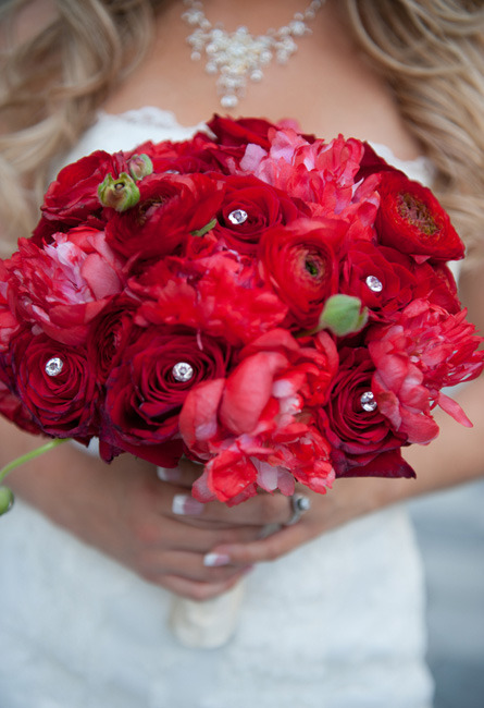 A bridal bouquet of delicious red roses, ranunculus, and fragrant peonies, accented with sparkling gems. Image by Kimbe Photography