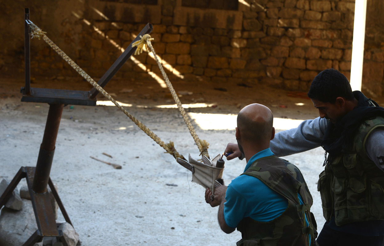 From DIY Weapons of the Syrian Rebels, one of 38 photos. Syrian rebels prepare to launch a bomb using a homemade slingshot in the northern city of Aleppo, on October 16, 2012. Lightly-armed Syrian rebels who face the warplanes, artillery and tanks of loyalists have turned to making their own weapons, even rigging a video game controller to fire mortar rounds. (Tauseef Mustafa/AFP/Getty Images)