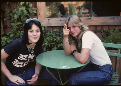 Joan Jett and Sandy West of The Runaways sitting at a green table at SIR in Hollywood about a million years ago.  Photo by Brad Elterman