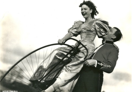 June Duprez rides a bike. John Clements gives a hand.
