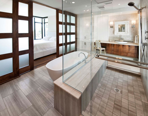 designed-for-life:  ensuite bathroom design by VOK group. It is a welcoming, modern space that encourages repose and well-being. What is interesting here is that the design doesn't need too much dressing up since the framework of the space provides enough interest. For example, the pale, wide plank wooden floors in the bathroom have been laid perpendicular to the direction of the dark wooden floor in the bedroom. Additionally, the direction of the wood grain between the tub and the shower is also different from the floor, although the color provides unity. There is enough contrast provided between the white of the walls and the tub against the different wood colors throughout the space. Therefore, this ensuite bathroom, governed mostly by rectangular shapes, can remain minimally adorned and still be stunning. The bedroom and bath areas are divided by a sliding door system made of wood and frosted glass, which wisely lets the light flow through both sides of the space, while maintaining privacy. http://www.trendir.com/interiors/ensuite-bathroom-design-by-vok-design-group.html