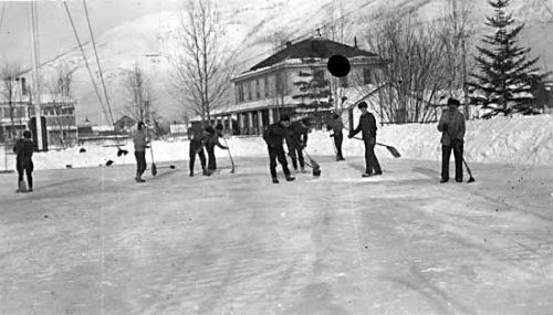 Nine men shoveling and sweeping off a rink at the RNWMP post at Dawson. Date 1917.