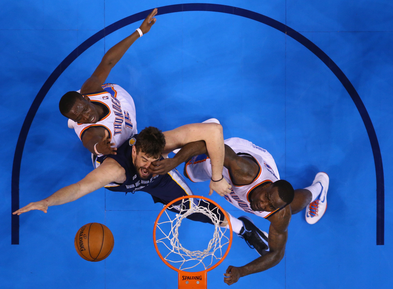 nationalpostphotos:  Full-contact NBA action — NBA playoff games are a different kind of games — grittier, more suspenseful and definitely more physical - just ask Marc Gasol #33 of the Memphis Grizzlies, who took a paw in the face while trying a shot against Reggie Jackson #15 and Kendrick Perkins #5 of the Oklahoma City Thunder during Game One of the Western Conference Semifinals of the 2013 NBA Playoffs at Chesapeake Energy Arena on May 5, 2013 in Oklahoma City, Oklahoma. (Photo by Ronald Martinez/Getty Images)