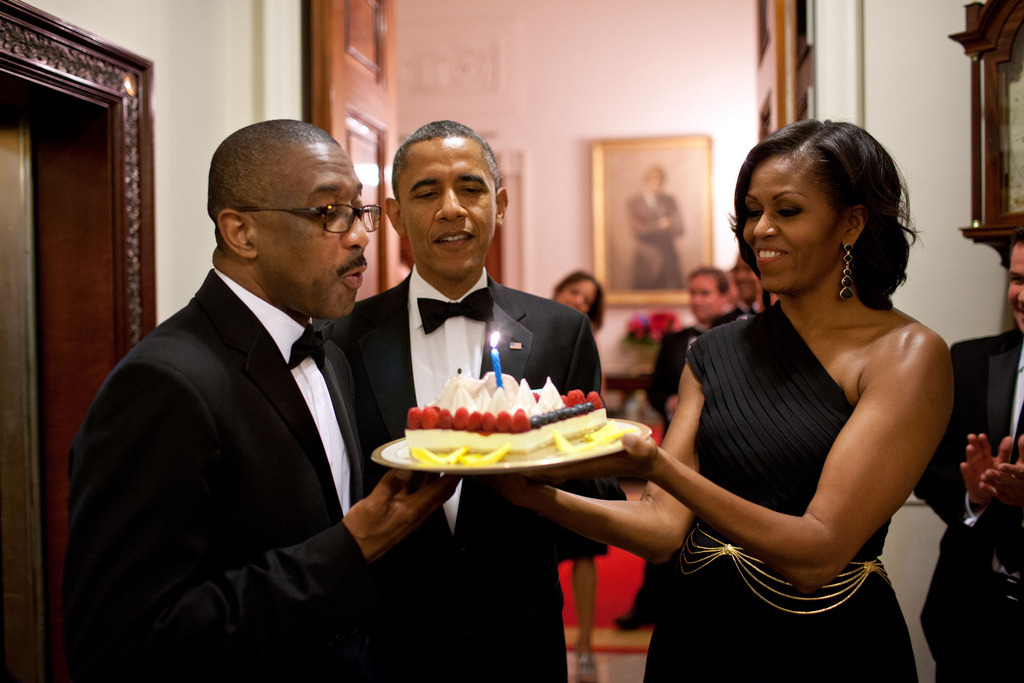 President Barack Obama and First Lady Michelle Obama present a birthday cake to Assistant Usher Reggie Dickson outside the Usher's Office of the White House, following a Presidential Medal of Freedom ceremony and dinner honoring President Shimon Peres of Israel, June 13, 2012. (Official White House Photo by Pete Souza) Most iconic Pete Souza photos of Obama family's first 4 years in the White House