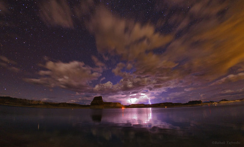 Lake Powell Stormy Night Storm clouds, lightening, and stars appear over Lake Powell, a reservoir on the Colorado River, straddling the border between Utah and Arizona. — Babak Tafreshi