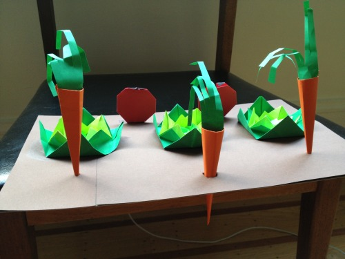 This week's Origami class project: Mini Garden! The lettuce/cabbage comes from a blintz base and then some folding upwards of the corners to create the 3D effect. The carrot model is my own design. I put holes into the chipboard (which is covered with brown paper) so the carrots could seem like they were growing up out of the ground. The tomatoes are my own design, too although they are a variation of a model which is probably already out there in Origami-land somewhere.  The tomatoes can easily become strawberries with one less fold at the bottom (in case the students prefer them over tomatoes).