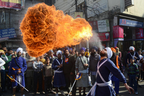 An Indian Sikh Nihang (warrior) performs a fire breathing act at a demonstration of gatka skills during a procession from Sri Akal Takhat to the Golden Temple in Amritsar on Nov. 27 on the eve of the 543rd birth anniversary of Sri Guru Nanak Dev. Guru Nanak was the founder of the religion of Sikhism and the first of ten Sikh Gurus. (Narinder Nanu/AFP/Getty Images) #