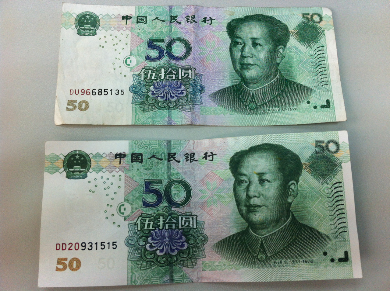 My first experience with fake Chinese money: Can you tell the difference between these two? It's nearly impossible and only by the texture of the paper can you tell the real from the  fake - it's the one on the bottom BTW. Even when you hold them to the light, they look exactly the same. Crazy how close the copies are! I now keep giving it to shops - not to con them -but to see if they can tell the difference. My poor barista at Starbucks was about to stick it in the register when I stopped her to point out its fakeness. With this game its only a matter of time before someone will take it for good without either of us knowing…