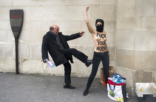 politics-war:  A man kicks a topless Femen activist, as she raises her fist to protest against Islamists in front of the Great Mosque of Paris, on April 3, 2013.