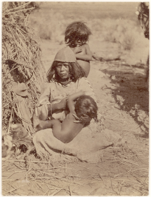 centuriespast:  Kaibab Paiute woman nursing a child while another child stands behind her. Woman wears a basketry hat and a fringed and beaded dress. Brush house (?) on the left. 1871-1873 John K. Hillers (Jack Hilliers/J.K. Hilliers), Non-Indian, 1843-1925, Edward O. Beaman, Non-Indian, 1837-1876, or James Fennemore, Non-Indian, 1849-1941 National Museum of the American indian
