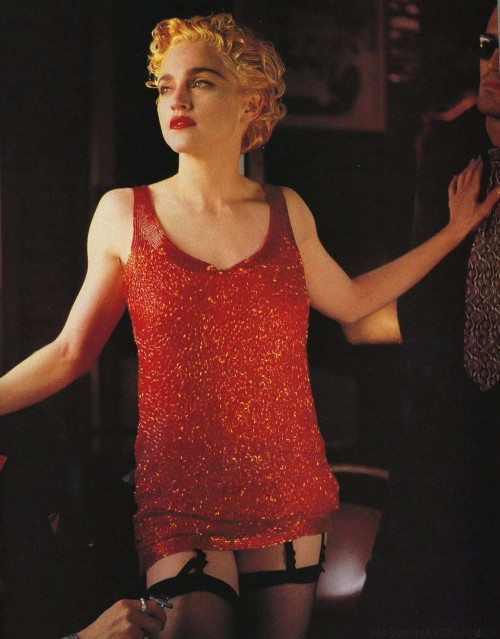 Madonna in bugle bead dress and black stockings shot by Helmut Newton 1990