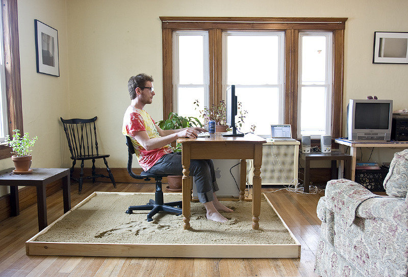 "inspirezme:  You thought your workspace was awesome? Not as awesome as Justin Kemp, I'm afraid. The Massachusetts-based art assistant has installed a sand pit for his feet to rest whilst he works away. His ""Surfing with the Sand Between My Toes"" concept consists of a wooden box lined with plastic on the bottom, filled with sand. This brilliant concept keeps Justin's toes feeling great and allows for a relaxing environment to work in. Justin explains his unconventional work place to us, ""The sand is relaxing, but for me, it's more a symbol of my permanent vacation.  It's the design of a lifestyle where 'work' becomes so satisfying that vacation and retirement become undesirable.  It's a permanent state of chill.""  Written by Andrew Murphy - Discovered on Inspirez (Full article here)"