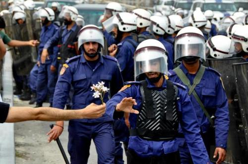 A demonstrator offers a flower to security forces during an anti-government protest in Bahrain, March 2011. Photo by Anmar Abdulrasoo.