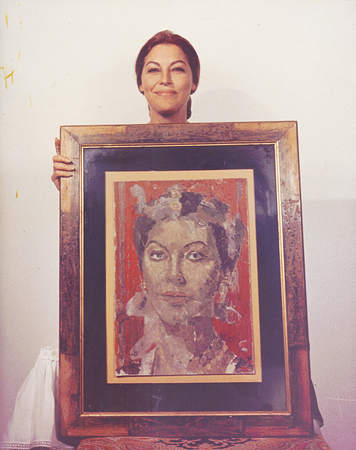 Ava Gardner stands with a portrait of herself, 1963.