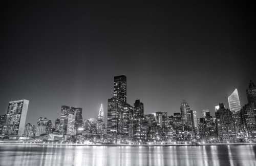 "New York City. Night skyline.—-  Night slides across the sky  like a trumpet's note falling over a syncopated rhythm  and the stars swoon and sway  mesmerized by the city lights  that pulsate to their own time signature.  —-  I have been traipsing all over the city for the last few months trying to capture a large majority of New York City's skyline views. I think everyone has a particular skyline view they immediately think of when they think of the city. And yet, it's still incredible to me after all this time that I come across different skyline angles that I hadn't previously come across or had the time to explore before from certain vantage points.  New York City has several prominent skyline views that are popular. One is in lower Manhattan and usually includes the skyscrapers of the Financial District along with the one or more of the bridges that serve the lower part of Manhattan. The other series of skyline views can be found from the top of a few popular skyscrapers in midtown Manhattan. Another series of skyline views involves the midtown Manhattan skyline as seen from different vantage points across (or in some cases directly from) the East River. This particular view is taken from one of the latter vantage points. It's a 30 second long exposure taken with the Sony A99 on a gorgeously clear and cold night in the beginning of March from Roosevelt Island.  Prominent skyscrapers in this view are the Chrysler Building and the United Nations building (all the way to the left). The lights of other famous midtown skyscrapers can also be seen even if those skyscrapers (looking at you Empire State Building) are hidden in this view. The lights directly in front of the skyscrapers that line the East River belong to the FDR Drive, a major traffic route that lines New York City's east side.   —-View this photo with a comment thread on my Google Plus page—-View ""New York City - Night"" in my photography portfolio here, email me, or ask for help."