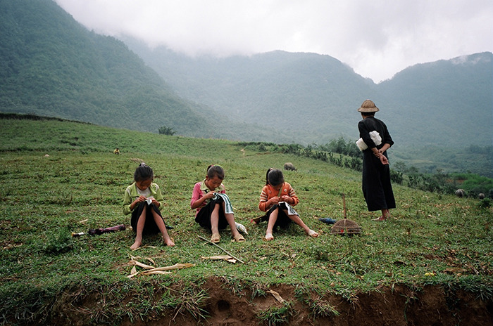 Sapa, Vietnam. August, 2012. Black H'mong children sewing.