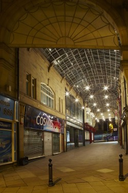 Pioneer House and Northgate Arcades Dewsbury,West Yorkshire for Kirklees Council, February 2013. Temporary lighting installations. Kirklees Council are currently applying to the Big Lottery Heritage Fund for monies to improve the built fabric of the historic northern end of Dewsbury town centre. Studio Dekka was commissioned to design and manage the installation of two temporary schemes to illustrate the bid at two key sites. Kingsway and Queensway Arcades link Northgate with the market and promise to be key east-west routes in a rejuvenated town centre. Despite being close to the busiest part of the town centre, they're currently underlit and can be threatening after dark. A simple design using bare lamps aimed to highlight the intricate ironwork of the arcade ceiling as well as making the route feel safer. Pioneer House is a grand Victorian building that dominates the northern approach to the town centre and the view of the town from the railway line. The building has fallen into disrepair over more than a decade and is currently being renovated by the local authority. The lighting installation aimed to suggest new activity after years of under-use around what is a substantial part of the town centre. Electrical Contractor: C&S Electrical Photography: Mark Sykes Photography