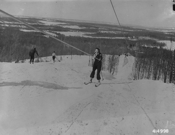 Ready to Hit the Slopes?  Approaching top of hill by ski tow. 1940-1941. Taken in the vicinity of the Huron-Manistee National Forests (Michigan). From the Historic Photographs file of the Forest Service's Eastern Region  The first rope tow ski lift in the United States began operation on January 28, 1934 outside Woodstock, Vermont.