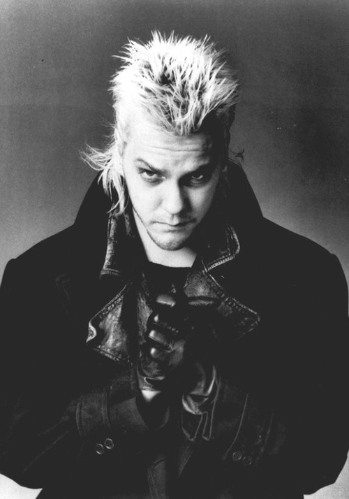 "Roots and Beginnings: The Lost Boys (dir. Joel Schumacher) Contra most of my writing about fantastic fiction as a rule-free zone, for whatever reason I always found the rules that governed vampires extraordinarily appealing as a storytelling device. I liked that there was an element of problem-solving that went along with tangling with these creatures, for them and for you; otherwise, with all their powers — transformation, telepathy, mind control, indestructibility, enhanced strength and senses, flight, intangibility, control over low animals, fangs — wouldn't the game be over before it began? I'm sure it helped that the first contemporary vampire movies I watched were The Monster Squad and (my very first R-rated movie) The Lost Boys, which made a lot out of the establishment of those rules in pop culture and what that would mean if you encountered vampires for real. To this day I find it super lazy for writers to have vampires walking around in the day (I know that's a Hollywood convention and not part of the traditional lore, but it is what it is), particularly since The Lost Boys proves how much tension and suspense can be drawn out from dancing right up to the point of no return and then using one of the rules to pull you back from the brink. Much of that tension, it must be said, is derived from how appealing David and his band of surf-punk-hair-metal vampires can be. Part of me retains a ten-year-old boy's skepticism about sexy vampires, but the look and lifestyle (and even the sound — remember their laughs? remember Kiefer Sutherland's sonorous growl of ""How far you willing to go, Michael?"") of the Lost Boys does not seem like a fate worse than death. Only when the mask comes off and they descend, like a pack of predatory animals, on innocents, rending and maiming and feeding, does the horror reveal itself. ""You never grow old, Michael. And you never die. But you must feed."" At times that seems like a small price to pay. It's only the rules that save you."