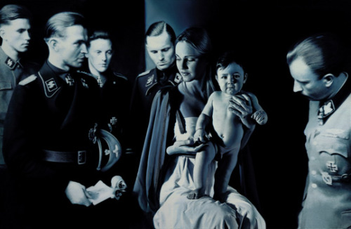 "mephistophelesisupset:  Gottfried Helnwein, ""Epiphany I (Adoration of the Magi)"", mixed media on canvas, 1996 his Austrian Catholic Nativity scene has no magi bearing gifts. Madonna and child are encircled by five respectful Waffen SS officers palpably in awe of the idealised, kitsch-blonde Virgin. The Christ toddler, who stands on Mary's lap, stares defiantly out of the canvas. Helnwein's baby Jesus is Adolf Hitler."