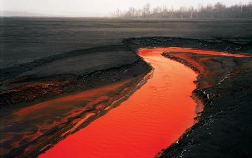 The Red River The chromatic colour and black barren land may appear to resemble that of a volcanic landscape, however this is a river in Sudbury, Ontario in Canada. This 'Red River' is the result of a nearby nickel factory, where the excess iron has seeped into the water and produced this deep red colour.  Despite it's fascinating hue this river is sadly an image of industrial pollution, where the contaminated water has prevented any life from growing in the rivers surroundings.