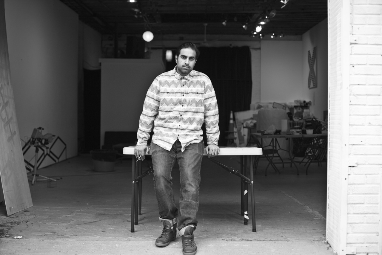 The Creators of NYC: Geometric Artist Aakash Nihalani Josh Wool spent a decade as an executive chef, opening restaurants across the south. But all that changed in 2010, when the carpal tunnel in his hands meant he could no longer work. To keep from going stir crazy, he picked up a camera and found his next calling. Two years, thousands of portraits, and a move to New York later, Wool is documenting the people who inspire him on a daily basis. Welcome to Creators of NYC. Aakash Nihalani Aakash Nihalani is at the forefront of the next generation of modern artists working in New York. His work in spray paint and tape can be found not only on the walls of private collectors but in and around the streets of New York. I met up with Aakash in his Williamsburg studio, where he was preparing for a solo show. How do you describe your art? It's hard … I usually direct people to look up an image on their phone. But I think at the barest, the work is about perspective, playing with our idea of three-dimensional space within a two-dimensional plane using tape as my primary medium, often in urban environments.  Why tape? I was part of a student exhibition where I exhibited a set of silkscreen studies involving the cube. I was using blue painter's tape to hang the prints and noticed that the shadow cast off of a nearby pedestal matched the shape in my prints. Instinctively, I outlined an isometric rectangle in the shadow with the tape. When I started using it outside, I found it was a great medium because I could put up a line, and if I didn't like it I could always just take it down … it's innocuous, I didn't have to damage anything to put up the art I wanted to see in the public. And after working on paintings in the studio for so long, the temporary nature of the tape was refreshing. How did growing up in New York influence you as an artist? I was born in Queens, but moved to Jersey when I was 2, so I mostly grew up in the suburbs. I came back to the city for college in 2004. I've always found New York to be a place to bust ass and believe in something different. What's a typical day like for you? My day usually depends on the project i'm working on. With the show coming up I've tried getting into more of a routine: work out in the morning, then head to the studio to work on paintings till … Where do you find inspiration? Everywhere really. I'm mostly just motivated by the need to keep making work and getting better. You're about to have your first solo show in Chelsea. Is there a lot of pressure that comes along with that? I don't think the pressure I feel is from the fact that it's in Chelsea, I'm excited about that. I'm more burdened with my own expectations of the work itself. What can we expect to see there? Large wall sculptures constructed from wood in a bold, bright palette. Paintings that shift foreground and background the longer you look at them. — Photos and text by Josh Wool