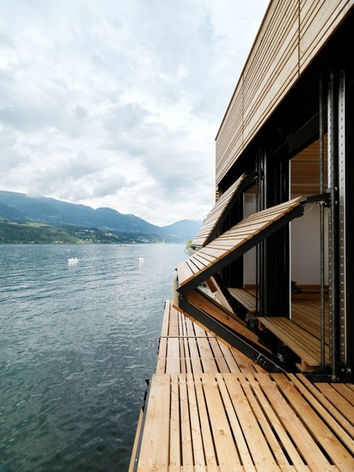 cjwho:  Folding wooden shutters on a house next to a lake