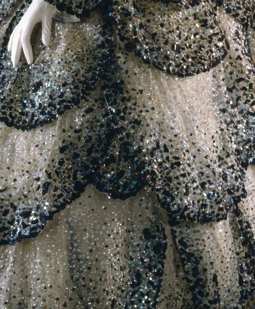 fashioninhistory:  'Junon' Evening Dress (Detail) Christian Dior Autumn/Winter 1949-50 'Junon', or Juno to the Romans, was more vividly conceived. The Magnificent skirt of forty-five petals, like abstractions of peacock feathers without their 'eyes,' obliquely references the bird associated with the queen of the gods. Each petal on the 'Junon' dress sparkles with iridescent sequins in varying shades of pale greens and blues to emerald green and navy blue, with sprinklings of rust.