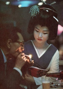 richmondcee:  Patron of Nightclub Uruwashi Having His Cigarette Lit by Geisha  This is surreal
