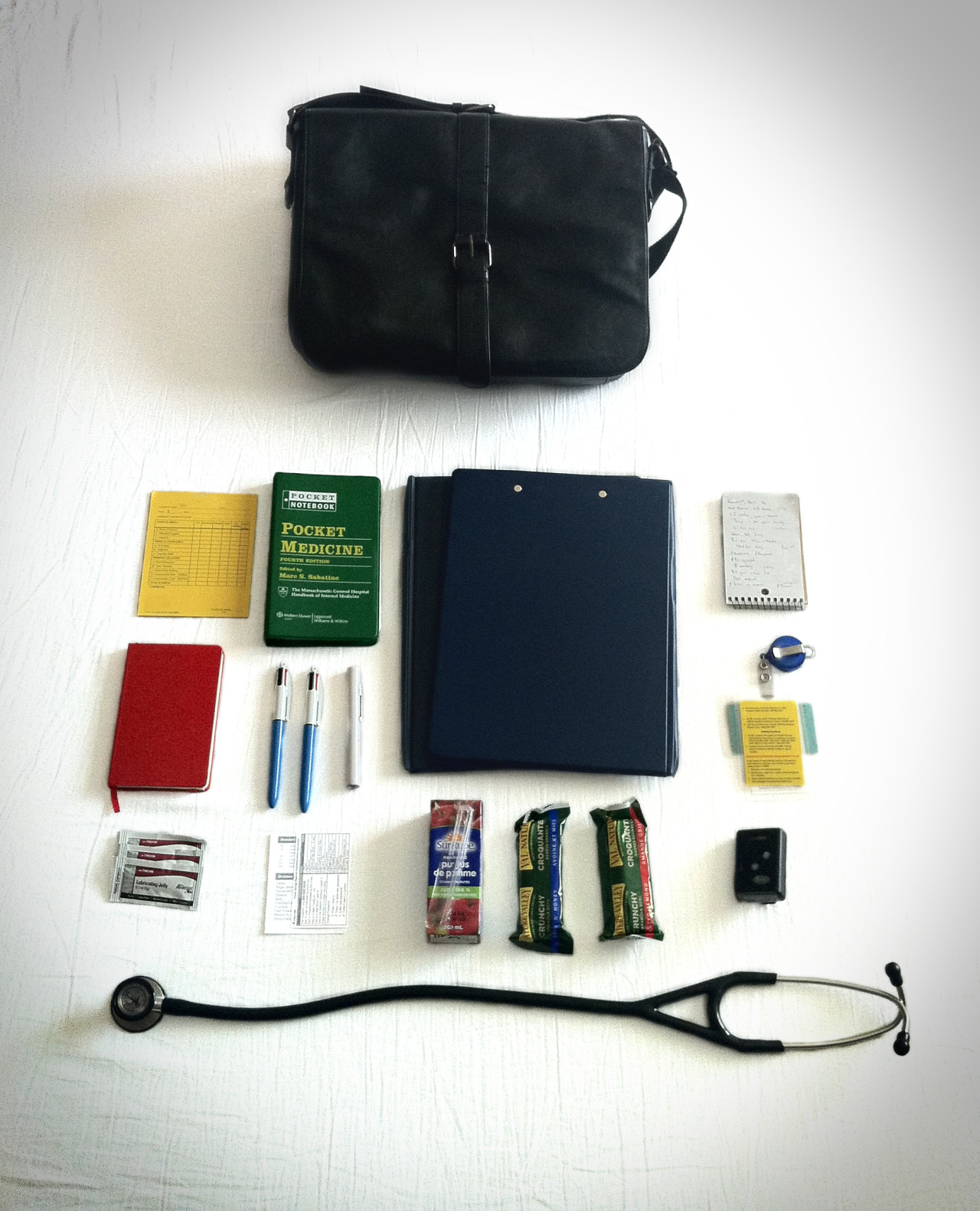 medicalstate:  The Satchel. Through thick and thin, my satchel has accompanied me through medical school. Initially, it strictly carried books and papers; now it is a repurposed bag for a clinical life. I talked briefly about what I usually carry with me in my first clinical pearl post. In response to Wayfaring MD's post, I thought I would share what I actually bring with me. These are my standard issue items, with room for switching or adding more items as needed: Satchel Pocket evaluation forms: For clinical skills and procedures. Pocket Medicine: A compact book for diagnostics, investigations and laboratory values. Two clipboards: The first contains regular paper for note taking including pre-printed progress notes and other chart-related forms; the second contains preceptor documentations including more formal evaluation sheets, outcomes checklists as well as my weekly schedule. The notepad: Where I write and gather my patient information and keep the to-do list for the patients I am responsible for. Moleskin notebook: Where I keep rotation specific clinical pearls and other tips and tricks. Two pens: Always keep a back up pen. Always. Pen light: For the quick neurological screen. ID cards Three packs of lubricating jelly: Need to do a digital rectal exam or a bimanual exam? Gloves are everywhere but these are not. Access codes and contact list Juice box Two granola bars Pager: How I wish this could not be standard issue. Stethoscope: If I am not walking around with it around my neck, it goes back into the bag until its next calling. Other items that I will sometimes include are rotation specific pocketbooks, headphones, and my phone charger to name a few. To the medical readers, what do you carry with you? Tag your response with #what's in your pocket.